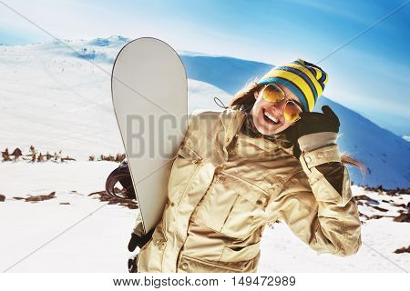 Happy girl snowboarder posing in sunglasses with snowboard
