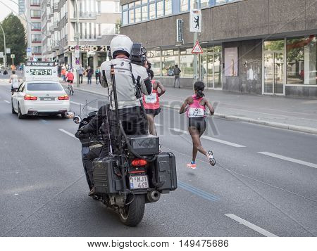 BERLIN GERMANY - SEPTEMBER 25 2016: Ethiopian marathon runner Aberu Kebede runs at Berlin Marathon 2016. Kebede wins this race. Cameraman on a motorcycle films her.