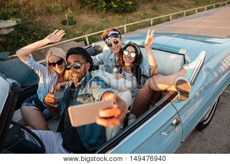 Group of happy young friends taking selfie with cell phone in the car