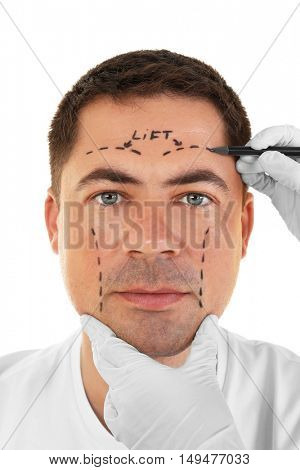 Plastic surgery concept. Hands in gloves marking male face