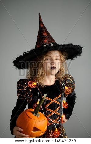 Portrait of the girl of 8-9 years in a suit for Halloween. She represents the evil sorcerer. The girl is dressed in a black-orange dress a hat. In hands at her pumpkin - Halloween symbol.