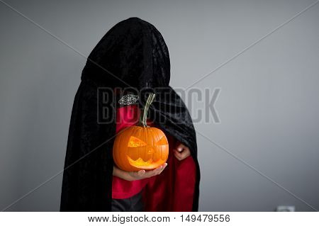 Child is dressed in black -red toga with hood. It is a costume for Halloween. He represents the mysterious wizard. The hood covers the face. Child holds pumpkin with a candle inside - Halloween symbol.