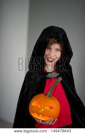 All Hallows Eve. Boy age dressed in a costume for Halloween. He represents the evil wizard. Boy is gowned in a black-red toga with a hood. He holds pumpkin with a candle inside - Jack o lantern