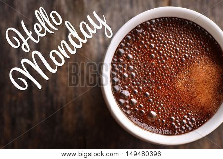 Text HELLO MONDAY and cup of aromatic coffee, closeup