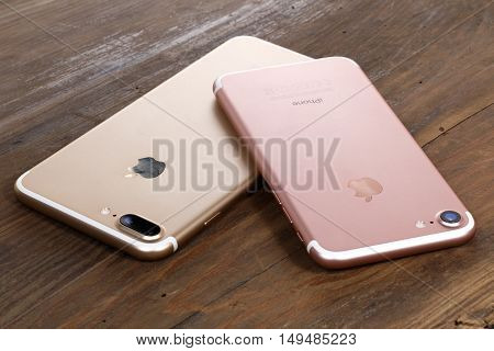 Koszalin, Poland - September 29, 2016: Golden iPhone 7 Plus and pink iPhone 7. Devices displaying the applications on the home screen. The iPhone 7 Plus and iPhone 7 is smart phone with multi touch screen produced by Apple Computer, Inc.