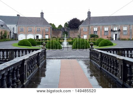 Court of castle with a water jet bushes and a bridge.