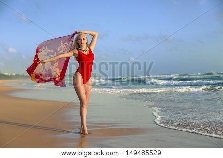 Pretty woman in the red swimsuit with long legs posing with pareo on the lonely evening beach in the rays of setting sun. Wide angle shot photo with double light exposition.