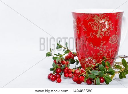 ripe lingonberries and red cup with ornament on white background