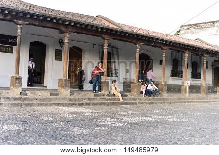 Antigua Guatemala - February 15 2015: Tourists and locals relax by one of the colonial buildings on the main plaza of Antigua Guatemala