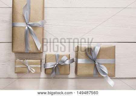 Top view of Gift boxes on white wood background. Presents in craft paper decorated with stylish elegant silver satin ribbon bows. Christmas and any other holidays concept, above view with copy space.