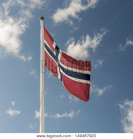 A Norwegian flag flutters in the wind against a blue sky background