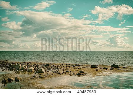 A seascape cloudscape image with a classic film camera style filter applied to it.