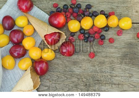 Ripe fruits - red plums and yellow alycha (cherry plum) in sugar ice cream cones on wooden background