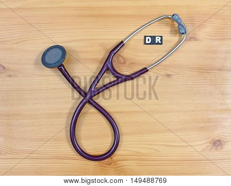 Purple cardiologist stethoscope with DR letters on wooden background