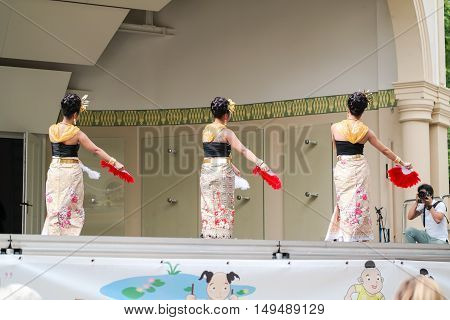 Group of Asian women in traditional Thai costumes dancing an oriental dance with the fans - July 31 2016, Thai festival