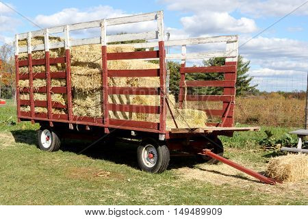 Rustic Old Red Hay Wagon in a farm field in fall