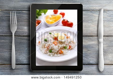 Table appointments and tablet. Photo of food on tablet screen.