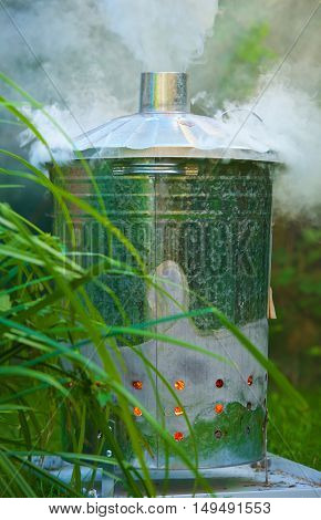 Burning Garden Waste in an incinerator. This photo was taken with the lid on showing more smoke billowing from the top