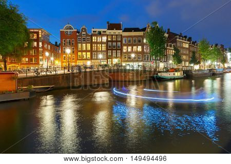 Amsterdam canal Prinsengracht with typical dutch houses, bridge and luminous track from the boat at night, Holland, Netherlands.