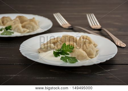 Pelmeni - Russian cuisine meat dumplings withe sour cream