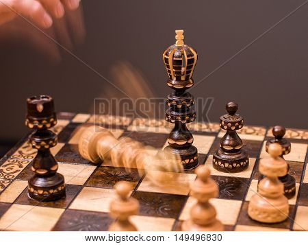 In a lost game of chess, the person playing white gives up the match and throws down the king.