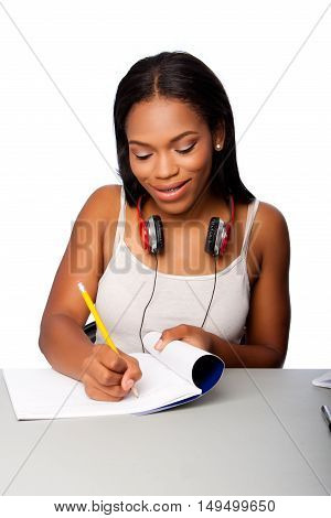 Cute beautiful happy smiling teenage student doing homework writing in notebook sitting at desk on white.