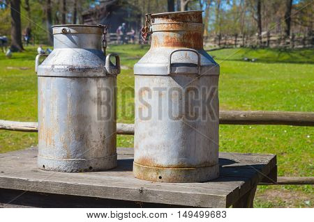 Two Metal Milk Churns On Wooden Table
