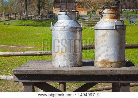 Metal Milk Churns Stand On Wooden Table