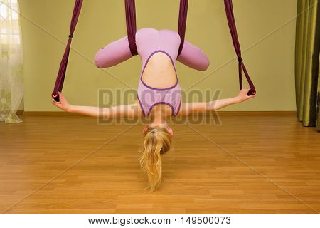Little girl making aerial yoga exercises, indoor, aerial yoga
