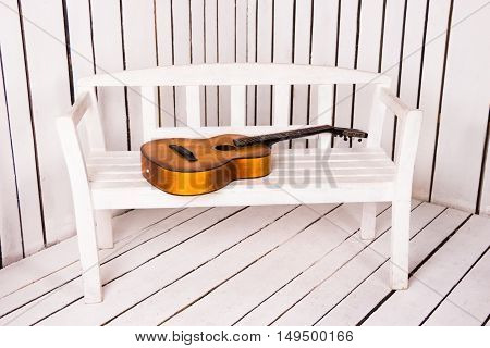 Acoustic guitar on the bench with abstract white wooden background
