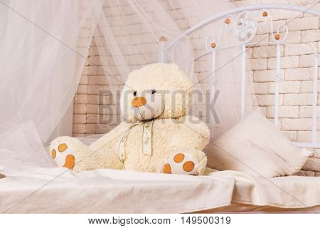 White teddy bear on the bed in the room