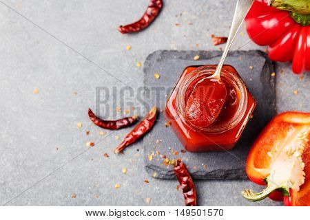 Sweet bell pepper and chili pepper sauce confiture jam in a glass jar. Grey stone background. Top view. Copy space
