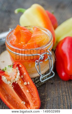 Bell pepper preserved in a glass jar with fresh peppers on old wooden background. Homemade marinated in oil red pepper. Glass jar with conserved roasted yellow and red paprika. Selective focus.