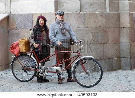 STOCKHOLM - SEPT 24 2016: Woman and man wearing old fashioned clothes in front of a tandem bicycle in Tweed event September 24 2016 in Stockholm Sweden