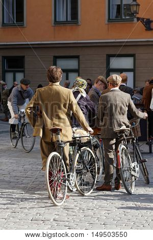 STOCKHOLM - SEPT 24 2016: Men with bicycles dressed in old fashioned tweed clothes in the Bike in Tweed event September 24 2016 in Stockholm Sweden