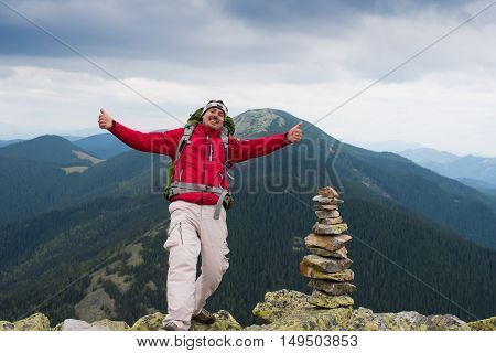 Happy hiker winning reaching life goal success freedom and happiness achievement in mountains. Thumbs-up. Hiker with backpack on top of a mountain.Concept of success. Stack of stones zen.