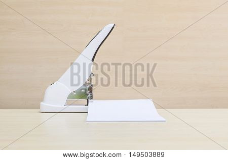 Closeup white stapler with white work paper office equipment on blurred wood desk and wall in office room textured background under window light