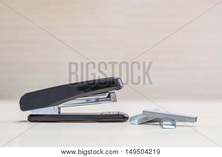 Closeup black stapler with staples office equipment on blurred wood desk and wall in office room textured background under window light