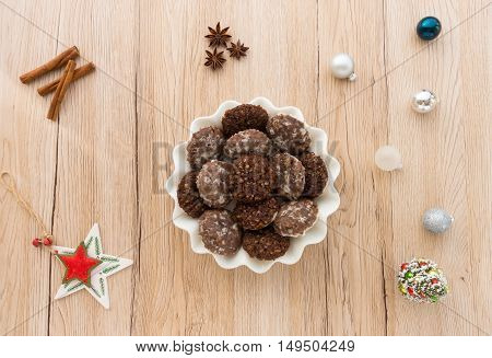 Homemade cookies with Christmas decoration on light brown wooden background. Shot from directly above.