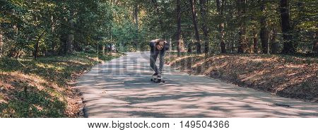 Skateboarder Ride A Longboard Through The Forest – Panorama