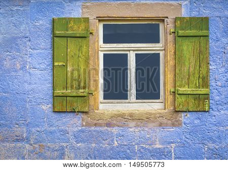 Window with wooden shutters  - Architectural details over a window with wooden shutters from an antique german house with walls painted in blue.