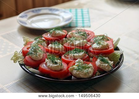sliced tomatoes with cheese and mayonnaise and garlic and dill on plate on table closeup