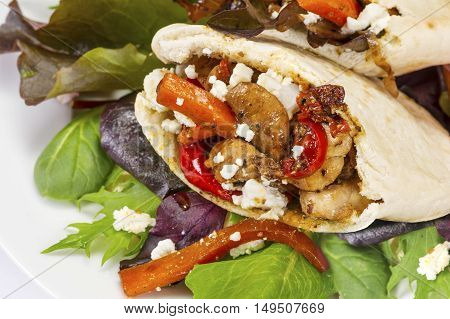 Delicious grilled chicken fresh salad leaves and fetta filling in warm pitta bread