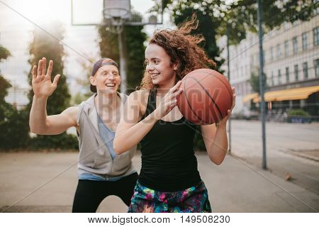 Young girl playing basketball with boy blocking. Teenage friends enjoying a game of streetball on outdoor court.