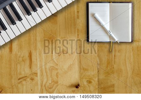 piano keys and notepad on wood table. composer music writer conceot.