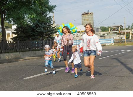 DNEPR, UKRAINE - AUGUST 24, 2016: Kids running with moms in Vyshyvanka Run during Independence Day local activity in Dnepr Ukraine at August 24 2016