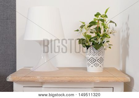 Nightstand with lamp and plant on a bright room