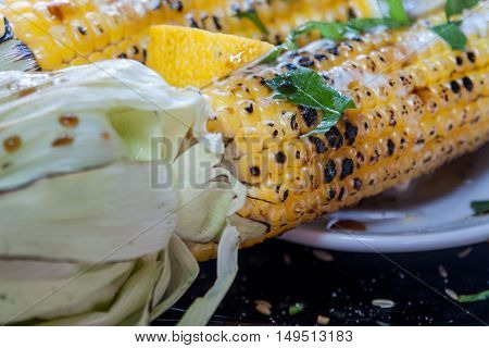 grilled corn on a wooden plate with lemon herbs and spices