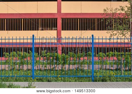 Blue fence on a background of pink walls multilevel parking lot in St. Petersburg in a sunny day.