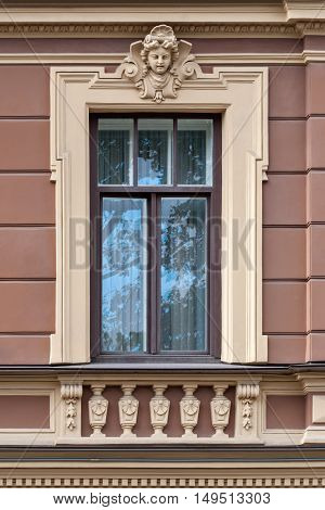 The facade of the building with walls of pink light and a window with a bas-relief. From the series window of Saint-Petersburg.